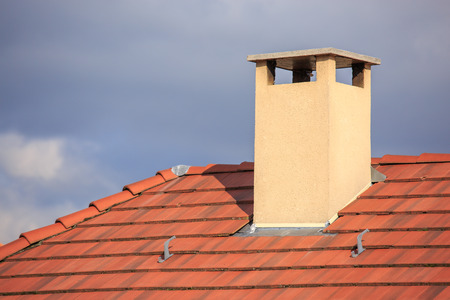 A close up  view of a chimney on top of red roof tiles Stock Photo