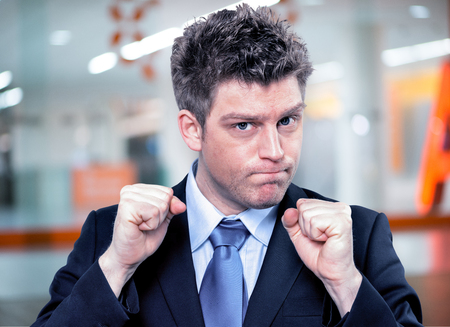 clenching: Closeup portrait of handsome businessman clenching fists to motivate team in office