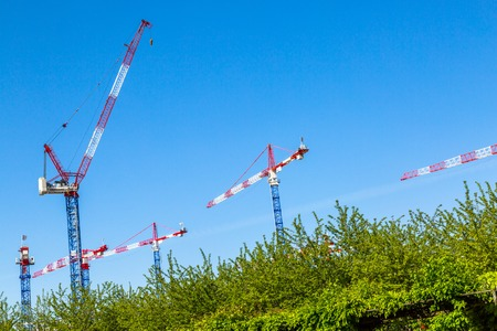 erecting: A number of cranes mounted on an empty land used for erecting buildings
