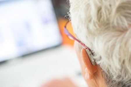 infotech: Close up of a senior person wearing glasses in front of a computer screen