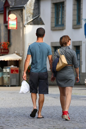 casually dressed: An Intimate couple casually dressed strolling down the street in the evening