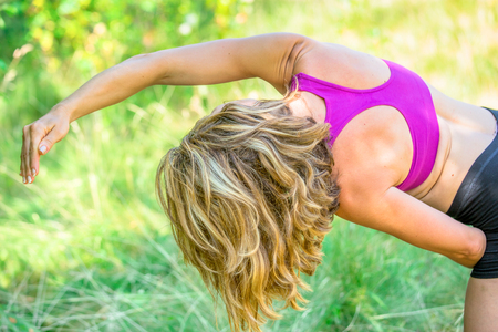 side angle pose: A woman in the extended side angle pose outside on a sunny day