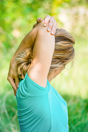 sporty woman stretching her triceps in a yoga position Stock Photo
