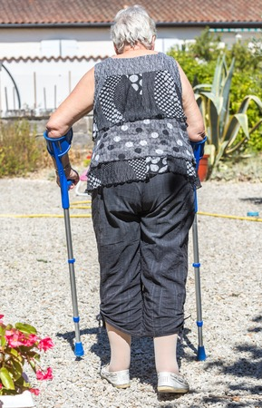 venous: Portrait of Senior woman walking with crutches in her garden