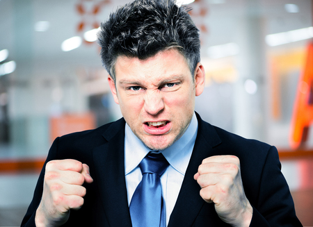 Closeup portrait of handsome businessman clenching fists to motivate team in office photo