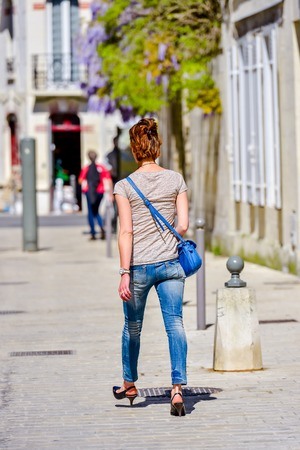 step well: Red-haired back turned girl walking on a boulevard in the daylight