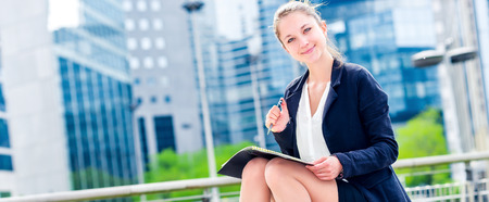openspace: panoramic view on dynamic young executive girl taking notes on her agenda, outside. Symbolizing a job search or a trade of outsourcing