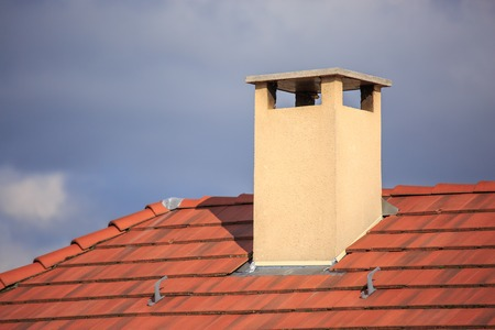 A close up view of a chimney on top of red roof tiles Imagens - 64802837