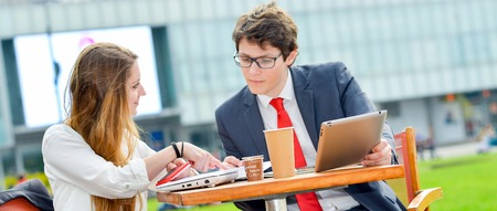 Young executive sales force team outdoors at a table. Commercial negotiation with customer Stock Photo