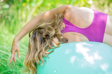 A woman performing the side- angle yoga pose with her head on the exercise ball.