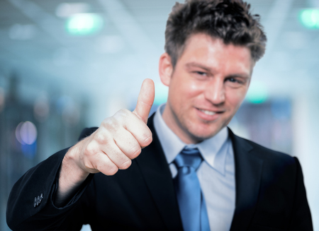 Portrait of Happy handsome business man holding thumbs up photo