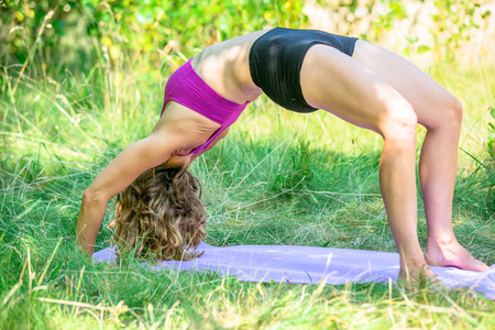 A woman inn an upward bow yoga posture outside in the afternoon Stock Photo