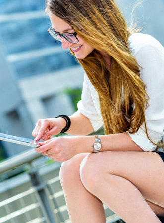 openspace: dynamic young executive girl working outside n a touchscreen tablet. Free of any constraint. Symbol of a job search or trade of outsourcing