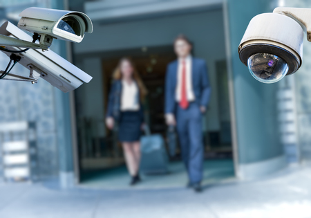 security CCTV camera or surveillance system with airport area and people on blurry background