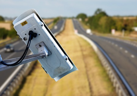 security CCTV camera or surveillance system with road highway on blurry background