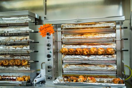pollo rostizado: suculentos pollos para asar en un asador en un mercado Foto de archivo