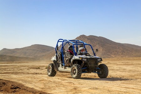 Merzouga, Morocco - Feb 24, 2016: Blue Polaris RZR 800 and pilots in Morocco desert near Merzouga. Merzouga is a small village located in the Saharan south-eastern Morocco. Merzouga is famous for its dunes, the highest in Morocco.