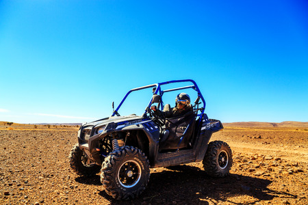 Merzouga, Morocco - Feb 23, 2016: Front view on blue Polaris RZR 800 with its pilot in Morocco desert near Merzouga. Merzouga is famous for its dunes, the highest in Morocco.