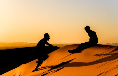 young man encourages his friend he managed to climb as high as him on a dune sahara