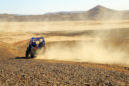 raid: Merzouga, Morocco - Feb 25, 2016: back view on blue Polaris RZR 800 with its pilot in Morocco desert near Merzouga. Merzouga is famous for its dunes, the highest in Morocco.
