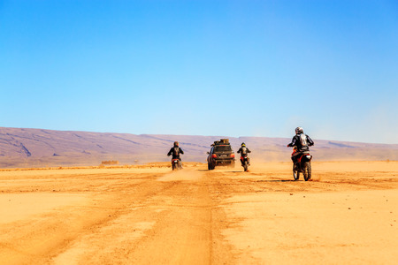 Merzouga, Morocco - Feb 22 2016: convoy of off-road vehicles (4x4 and motorbikes) in Morocco desert near Merzouga. Merzouga is famous for its dunes, the highest in Morocco.