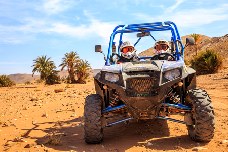 Merzouga, Morocco - Feb 26, 2016: front view on blue Polaris RZR 800 with its pilots in Morocco desert near Merzouga. Merzouga is famous for its dunes, the highest in Morocco. There is a palm grove in the background