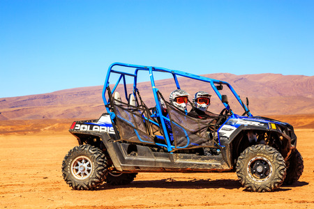raid: Merzouga, Morocco - Feb 22, 2016: Side view on blue Polaris RZR 800 with its pilots in Morocco desert near Merzouga. Merzouga is famous for its dunes, the highest in Morocco.