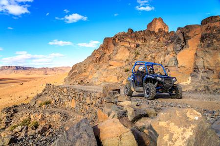 Merzouga, Marruecos - el 21 de Feb, 2016: Polaris RZR 800 azul cruzando una carretera de montaña en el desierto marroquí cerca de Merzouga. Merzouga es famoso por sus dunas, las más altas de Marruecos. Foto de archivo - 64694662