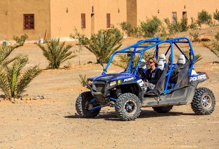 polaris: Itrane, Morocco - Feb 24, 2016: blue Polaris RZR 800 with woman pilot in a small Berber village in Morocco desert near Merzouga Editorial