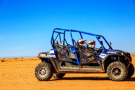 Merzouga, Morocco - Feb 23, 2016: Side view on blue Polaris RZR 800 with its pilots in Morocco desert near Merzouga. Merzouga is famous for its dunes, the highest in Morocco.