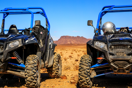 raid: Merzouga, Morocco - Feb 21, 2016: blue Polaris RZR 800 aligned and stationed with no pilot in Morocco desert near Merzouga. There is a great mountain in the background Editorial
