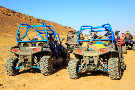 Merzouga, Morocco - Feb 24, 2016: back view on blue Polaris RZR 800 group of pilots with bickers and quad in Morocco desert near Merzouga. Merzouga is famous for its dunes, the highest in Morocco.