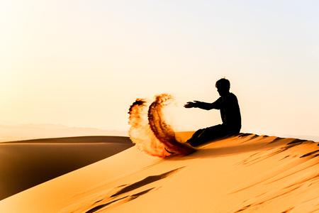 Silhouette de jeune homme jouant avec le sable sur une dune du sahara Banque d'images - 64845769