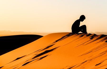 Silhouette des jungen Mannes Meditation über der Spitze einer Düne von sahara sitzen Standard-Bild