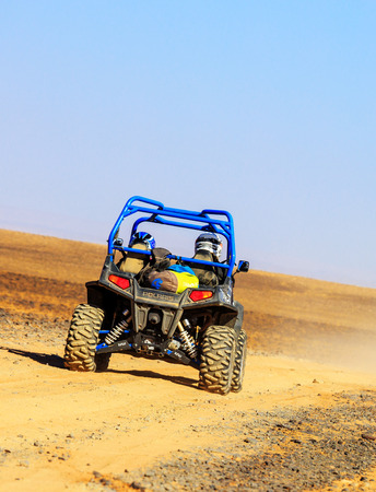 Merzouga, Morocco - Feb 25, 2016: back view on blue Polaris RZR 800 with its pilots in Morocco desert near Merzouga. Merzouga is famous for its dunes, the highest in Morocco. Editorial