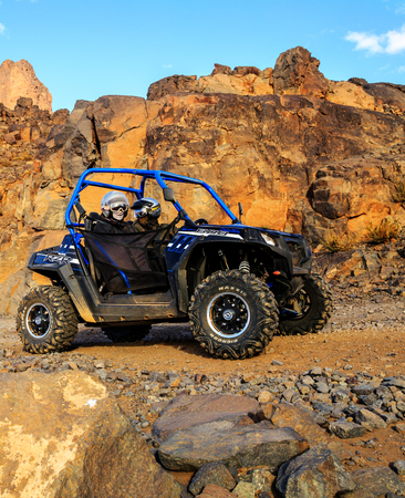 raid: Merzouga, Morocco - Feb 21, 2016: blue Polaris RZR 800 crossing a mountain road in the Moroccan desert near Merzouga. Merzouga is famous for its dunes, the highest in Morocco.