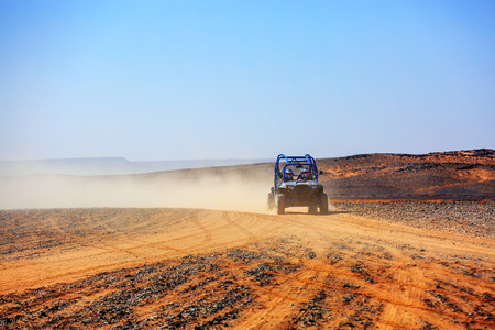 off road car with it's pilots in Morocco desert near Merzouga