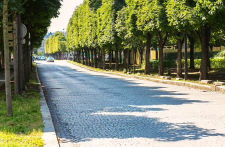 Paris, France - Jul 14, 2014: large paved tree-lined road with no traffic near the fields Elysees avenue Editorial