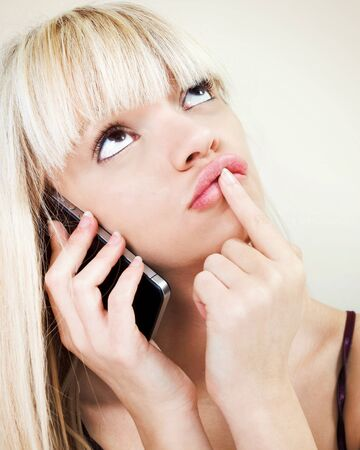 Portrait of pretty blond girl Portrait of pondering while phoning Stock Photo