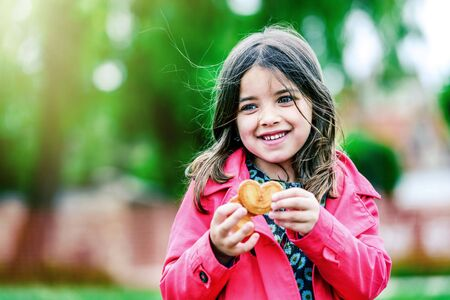 cute girl with cookies in the hands and greenery on background Stock Photo