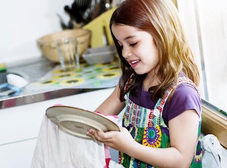 非常にかわいい女の子が台所でお皿を拭く 写真素材