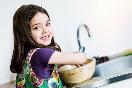 sehr nettes Kind Mädchen Geschirr in der Küche zu tun