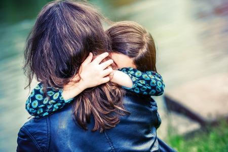 Mooi meisje knuffelen haar moeder met water op de achtergrond