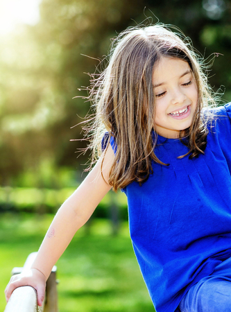 scaling: beautiful portrait of cute child playing with greenery in the background