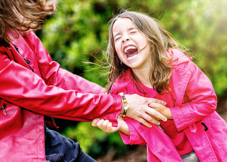 complicity: the complicity of happy pretty little girl playing with her mother Stock Photo