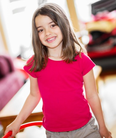 Glückliches nettes Kind mit einem Band in den Händen, die in einem Wohnzimmer stehen
