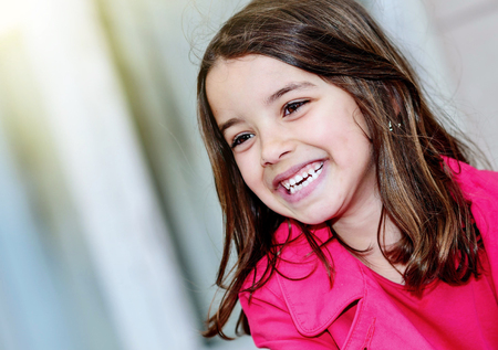 natural portrait of a smiling and happy pretty little girl