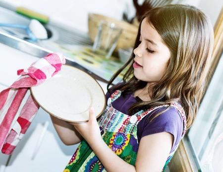 sehr nettes Mädchen, das Geschirr in der Küche Abwischen