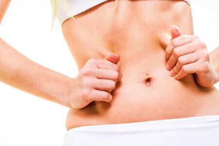 pinching: attractive female pinching skin of her belly Stock Photo