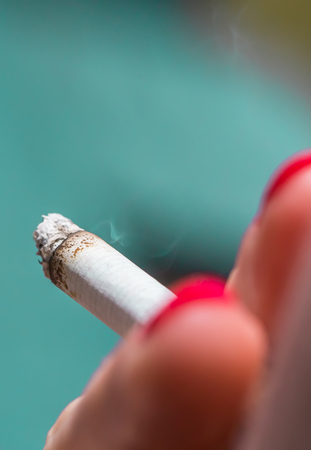 A woman with red painted nails smoking a cigarette outside.